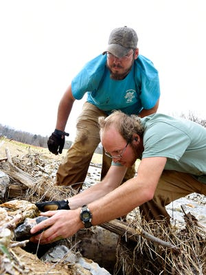 Willie Clark, front, and Kenneth Barker, both with Aquatic Resource Restoration Company based in Seven Valleys, move rocks around to build up revetments to absorb the energy of incoming water at the curving points of a natural spring in the developing wetland project at Richard M. Nixon County Park in York, Monday, April 4, 2016. Dawn J. Sagert photo