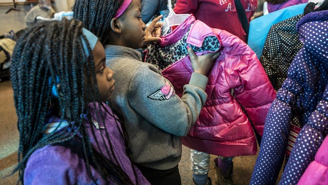 The Salvation Army has begun accepting applications for its Christmas Cheer Program, through which families can receive assistance this Christmas.  Blessing Haile and her older sister, Daejahnae pick out winter coats at the Salvation Army coat drive Thanksgiving Day 2015.