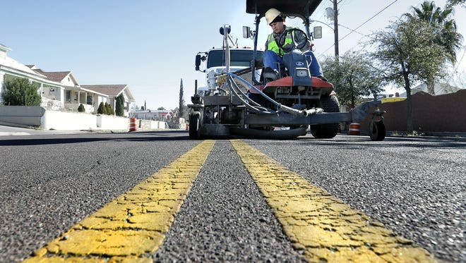 Ray Escalante of Bowen Industrial Contractors removes street markings Monday along Tularosa Avenue in Central El Paso. The city is creating angled parking in the area. Tularosa Avenue will see an increase of 26 parking spaces and Pershing will receive an additional 12. The spaces are being created to accommodate the increase in businesses in the Five Points area.