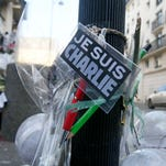 Flowers are laid near the headquarters of magazine Charlie Hebdo in Paris on Friday, Feb. 6, following the a terror attack at the offices of French satirical publication Charlie Hebdo on Jan. 7.