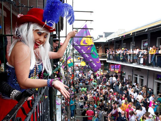 Malia Miyashiro of California throws beads from a Bourbon Street balcony to Mardi Gras revelers in French Quarter in New Orleans on Feb. 17, 2012.