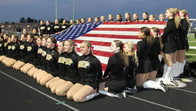 Southeast Polk Rams Rhythamettes hold the American flag before the Rams played Des Moines East at Rams Stadium. The Rams beat the Scarlets 52-0.