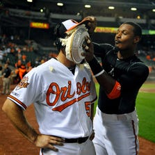 Sep 3, 2014; Baltimore, MD, USA; Baltimore Orioles starting pitcher Miguel Gonzalez (50) gets a pie in the face from Adam Jones after pitching a complete game shutout against the Cincinnati Reds at Oriole Park at Camden Yards. The Orioles defeated the Reds 6-0. Mandatory Credit: Joy R. Absalon-USA TODAY Sports