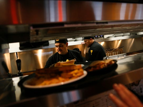 Denny's line cook Robert Robles, left, works on an