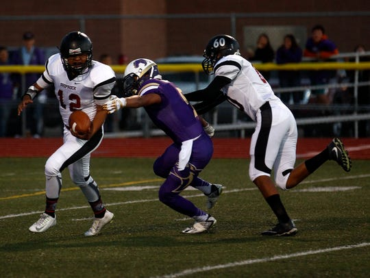 Shiprock quarterback Aawin Chee scrambles to avoid