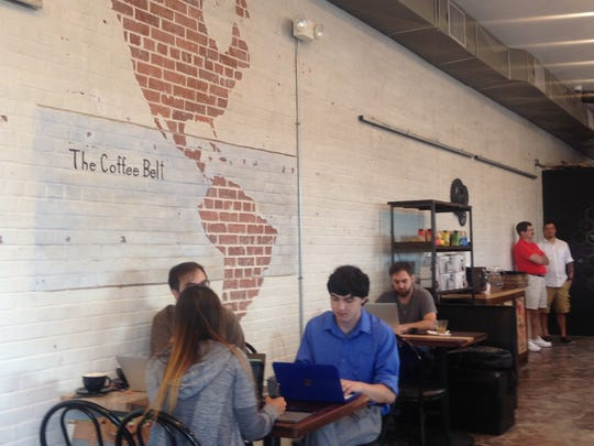 "A wall inside of the new location of Reve Coffee Roasters shows ""the coffee belt,"" or the region of the world where coffee beans come from."