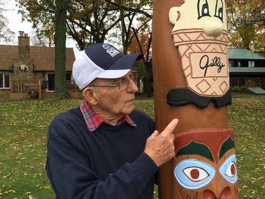 Tom Gilles points to the Gilles Custard mascot he carved into his 15-foot totem pole. The artwork stands on the shore of his Lake Deneveu home.