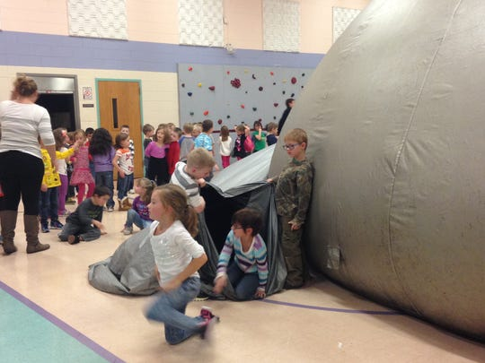 First graders at Millside Elementary School in Algonac crawl out of a tunnel leading to a travelling sky dome planetarium, set up in the school's gymnasium.