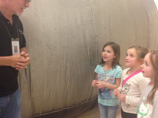 David Killion, a presenter with mobile ed productions, inc., talks with Millside Elementary first graders Lilly Steck, Sterling Roberts, and Olivia Voorhies after a travelling planetarium show at the school on Tuesday.