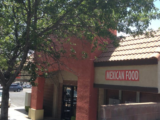 A sign on the side of the building that houses Prowess Cafe, advertises Mexican food.