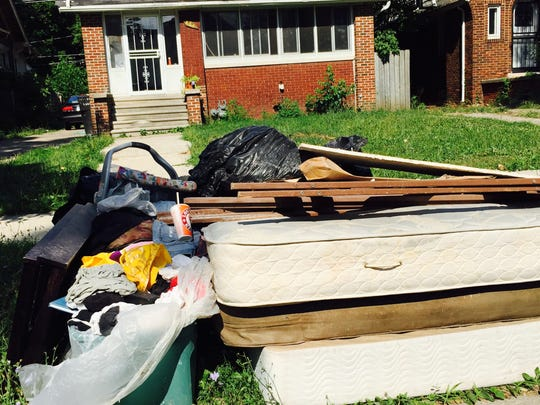 Belongings ruined in recent basement flooding are piled in front of a house on Detroit's far east side.