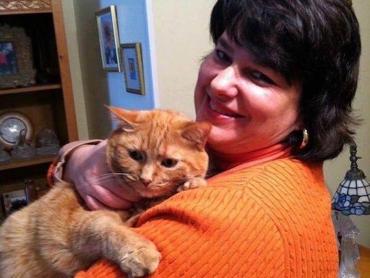 Jennifer Burke and her cat Hippie Chick. The big orange