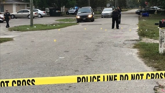 FMPD crime scene technicians examine shell casings on Belmont Street following an  early morning shooting Tuesday. Two people were taken to an area hospital.