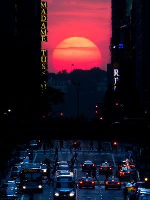 """The sun sets along 42nd Street in Manhattan during an annual phenomenon known as """"Manhattanhenge,"""" when the sun aligns perfectly with the city's transit grid,  May 29, 2013, in New York."""