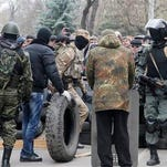 Armed pro-Russian activists occupy the police station and build a barricade as people watch on, in the eastern Ukrainian town of Slovyansk on Saturday.