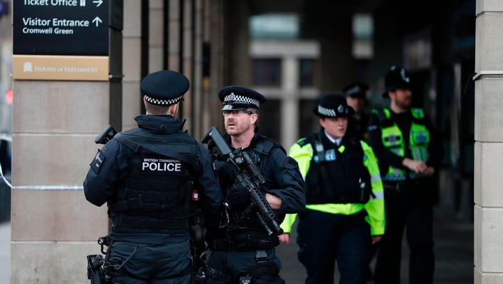 Armed police secure the area across the road from the