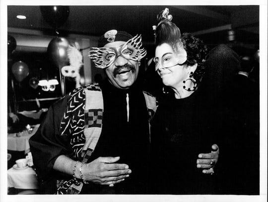 Garth Fagan greets Elaine Simon at a masked ball celebrating