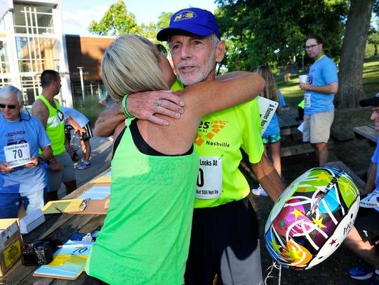 Peter Pressman gets a hug from Kellie Arrant on Aug.