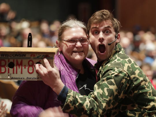 Comedian Charlie Berens poses with the woman who paid