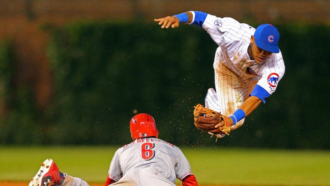 Cincinnati Reds center fielder Billy Hamilton (6) steals second base with Chicago Cubs second baseman Addison Russell (22) attempting the tag during the tenth inning at Wrigley Field.