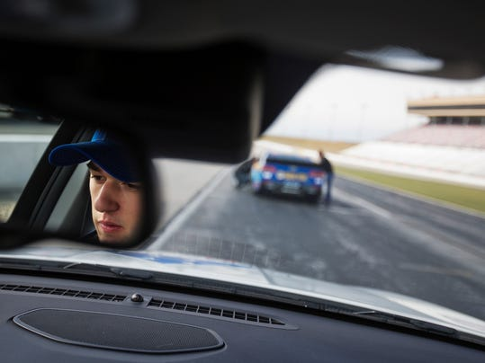Chase Elliott is seen in a rearview mirror as he waits to drive a pace car around the Atlanta Motor Speedway track Monday, Feb. 15, 2016, in Hampton, Ga. One day after becoming the youngest to win the NASCAR Daytona 500 pole, Chase Elliott returned home for an appearance Monday at the Atlanta Motor Speedway track, where the Elliott Grandstand honors his father. (AP Photo/David Goldman)