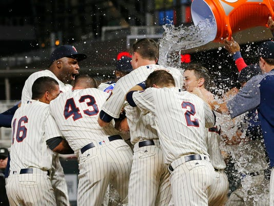 Minnesota Twins' Eddie Rosario is surrounded by teammates and gets a water shower after his two-run walk-off home run against the San Diego Padres during the 10th inning of a baseball game Wednesday, Sept. 13, 2017, in Minneapolis. The Twin won 3-1. AP Photo/Jim Mone)