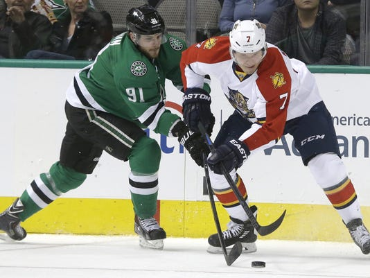 Florida Panthers defenseman Dmitry Kulikov (7) and Dallas Stars center Tyler Seguin (91) skate for the puck during the first period of an NHL hockey game Friday, Feb. 13, 2015, in Dallas. (AP Photo/LM Otero)