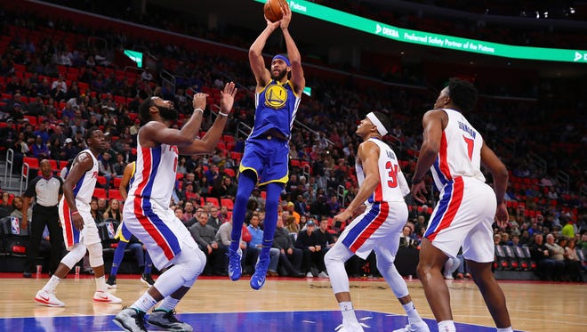 JaVale McGee #1 of the Golden State Warriors takes a first half shot next to Andre Drummond #0 of the Detroit Pistons at Little Caesars Arena on December 8, 2017 in Detroit, Michigan.