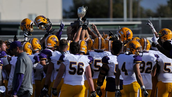 The Hardin-Simmons University Cowboys hold the Wilford Moore Trophy overhead after winning their game against McMurry University on Saturday Nov. 11, 2017. The final score was 28-0, HSU.