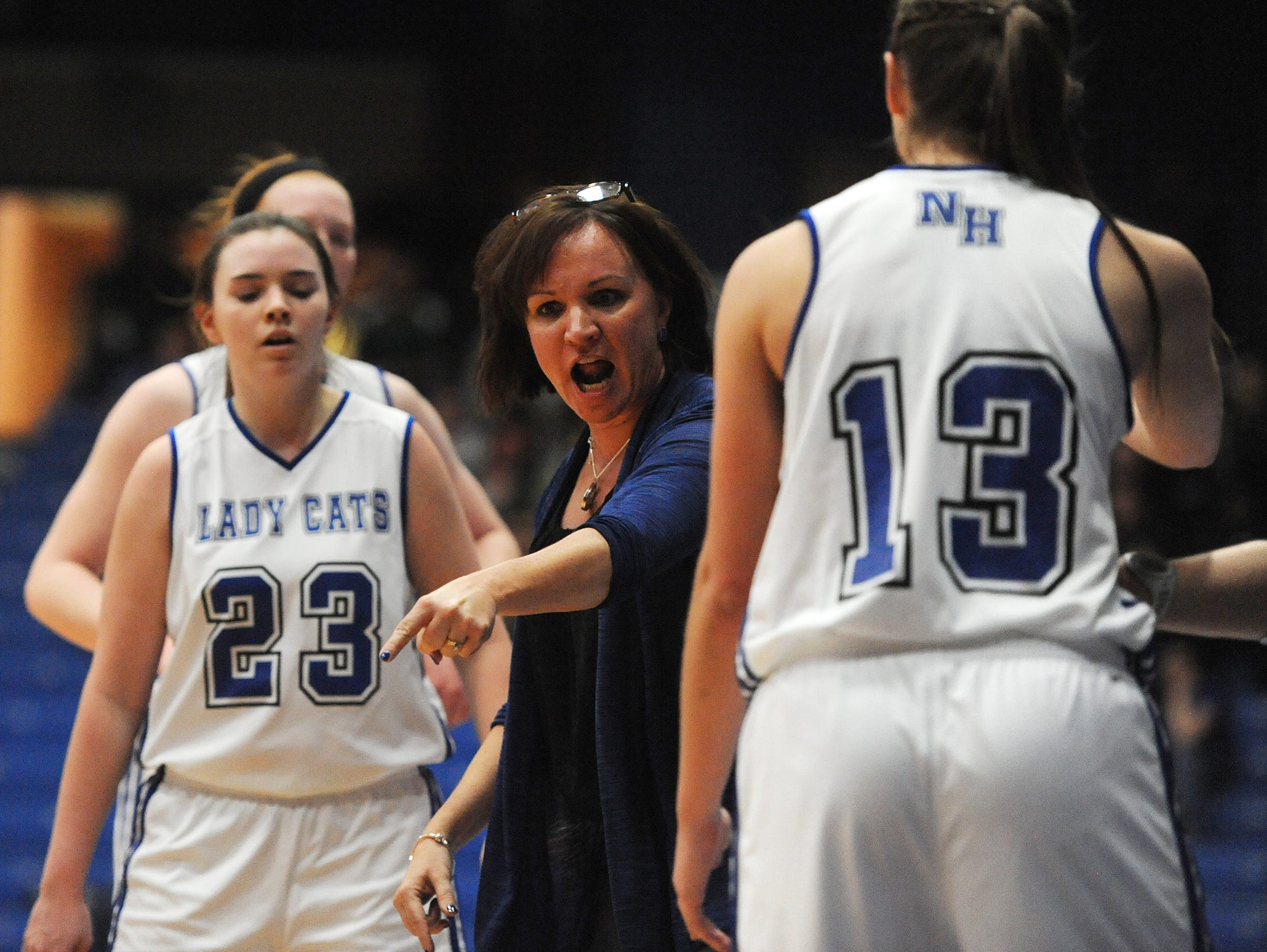 North Harrison head coach Missy Voyles (center) gives her Lady Cats instructions during a timeout against Greensburg on Saturday during the Regional 8 Tournament at Charlestown High School. North Harrison won 46-42. Photo by David Lee Hartlage/Special to the Courier-journal. Feb.13, 2016