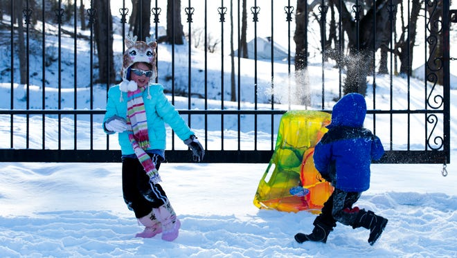 Reagan Miller, 8, and her brother Matthew, 3, have a snowball fight at Emerald Hill on January 16, 2018.