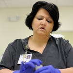 Adena Occupational Health Coordinator of Alcohol and Drug Testing Melissa Davis goes through paperwork with a patient so they know where their test is going to be analyzed and when they should have the results of the test.