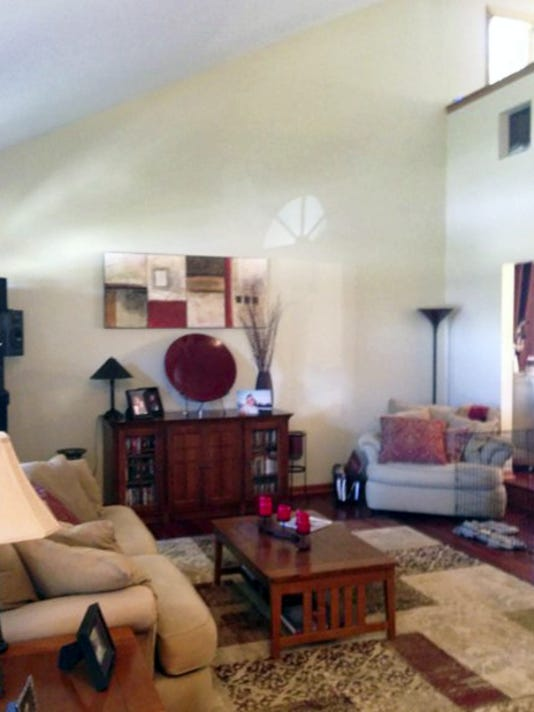 BEFORE: This family room with a tall, slanted wall still has an unfinished look, no matter how full of furnishings.
