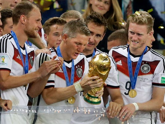 FILE - In this July 13, 2014 file photo Germany's Bastian Schweinsteiger looks at the trophy after the World Cup final soccer match between Germany and Argentina at the Maracana Stadium in Rio de Janeiro, Brazil. Germany beat Argentina 1-0 to win the World Cup. Germany captain Bastian Schweinsteiger said Friday, July 29, 2016 he is quitting the national team. The 31-year-old said in a Twitter statement that he's asked Germany coach not to include him in the line-up in future.  (AP Photo/Victor R. Caivano, file)
