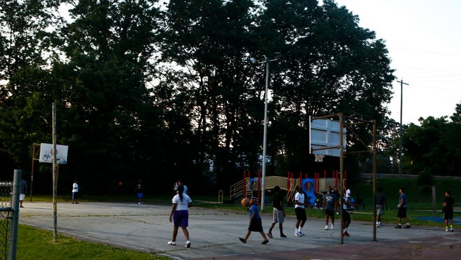 The basketball court is busy with young people, mostly teens, playing as the sun sets before 9 p.m. in Woodlawn Park in Wilmington Monday.