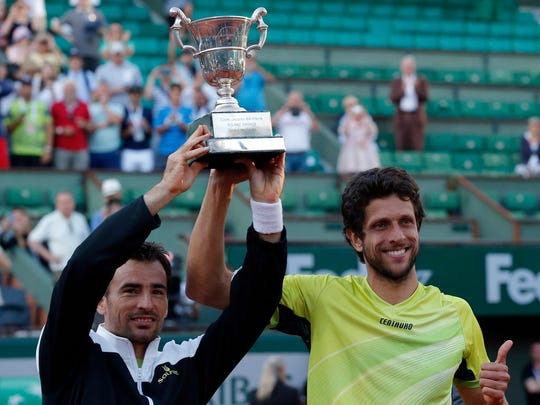 Croatia's Ivan Dodig, left, and Brazil's Marcelo Melo pose with their trophy after defeating Bob and Mike Bryan of the U.S. in their men's doubles final match of the French Open tennis tournament at the Roland Garros stadium, Saturday, June 6, 2015 in Paris. Dodig and Melo won 6-7, 7-6, 7-5.  (AP Photo/Michel Euler)
