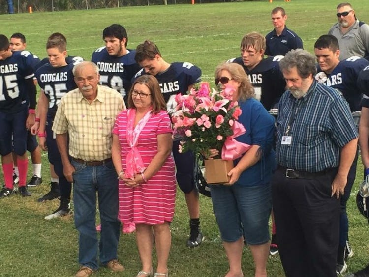 MIC football presented flowers to (left to right) Dennis Brogdon, Paula Brogdon, Sue Cottrell and Tim Cottrell in recognition of Breast Cancer Awareness.