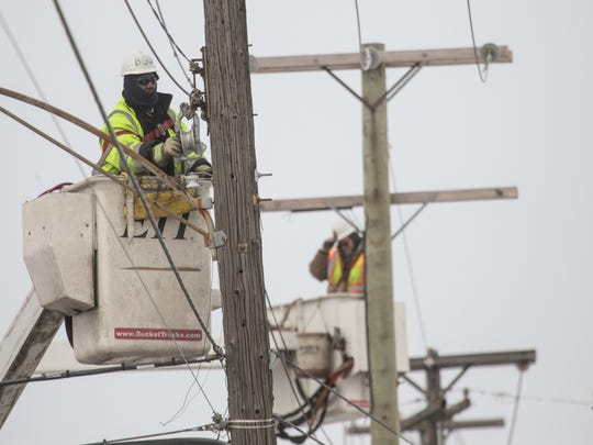 Linemen work on swapping out old street lights for new LED fixtures along Conant in Detroit on Wednesday, March 4, 2015.