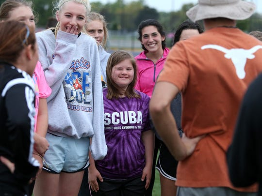 Katie Ball, center, a senior at Waukee, practices with classmates for the upcoming Powder Puff football game, part of the 2014 homecoming activities at Waukee High School.