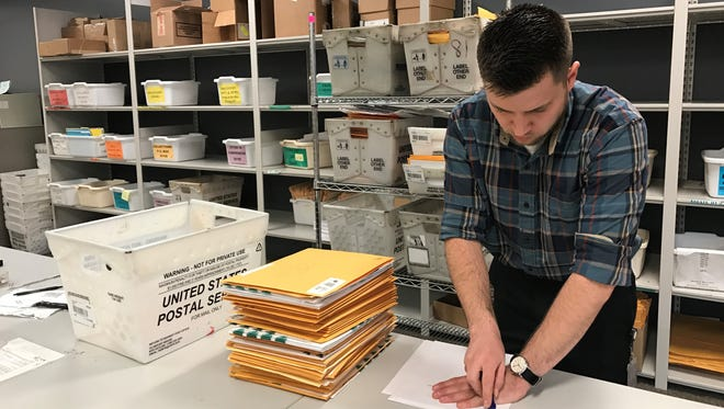This photo provided by the Michigan Treasury shows a Treasury employee removing staples on incoming documents before sending them to document processing for scanning.
