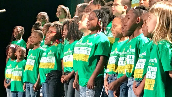 Children from the Emerald Youth Foundation sing during Friday morning's 25th anniversary breakfast.
