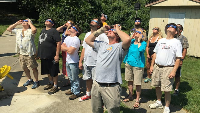 Visitors and members of the Cincinnati Astronomical Society use glasses to view the Aug. 21, 2017, solar eclipse at the society's Cleves observatory.