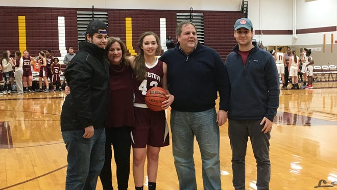 Morristown senior point guard Elizabeth Strambi is congratulated by her parents, Debbie and Steve, and brothers Steve and Matt, after scoring her 1,000th career point on Friday.