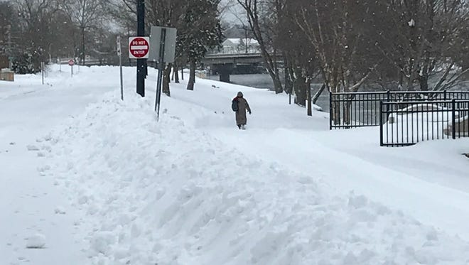 A Wisconsin Rapids woman decides to brave a hike through the snow, rather than drive her car to work Monday morning, April 16, 2018.