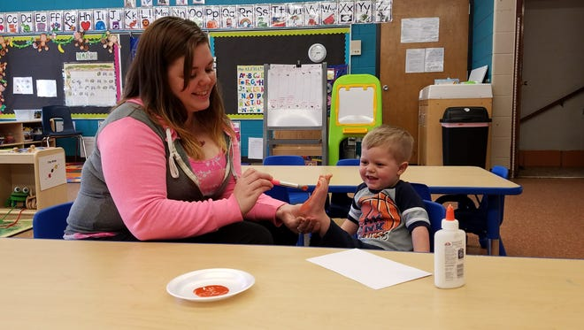 Sue Wisswell paints the foot of her son Ethan during an activity at Literacy and Beyond's 2Gen Learning Center.