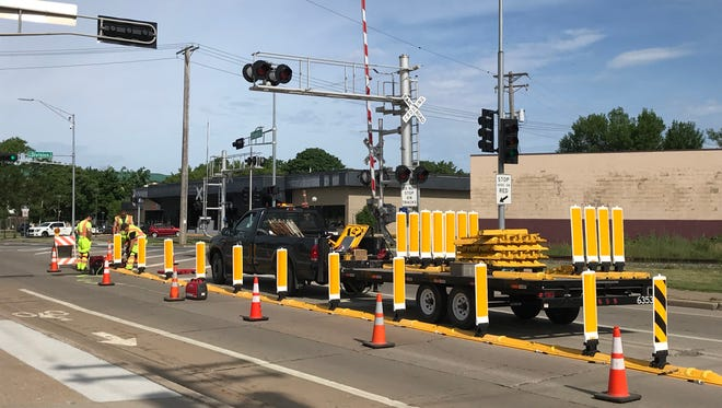 Workers install barriers at the intersection of Franklin and Division streets in Appleton to prevent drivers from going around closed gates at the railroad crossing.