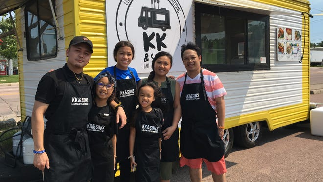 Mikey Siyawong, left, and Tiou Xayavong, right, and family pose in front of their food truck, KK & Sons Lao & Thai Food.