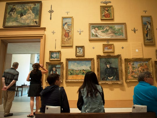 Visitors view art pieces displayed in the main gallery