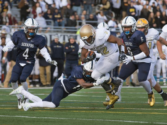 Mater Dei's Eddie Lewis and team mate Jowan Mitchell bring down  Holy Spirit's Reginald Jean Charles as he tries to make yardage up the middle. Mater Dei Prep vs Holy Spirit in NJSIAA Non-Public Group II Championship football game at Kean University in Union, NJ