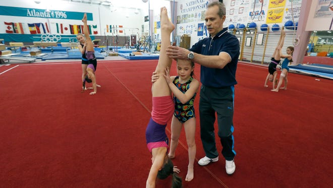 Coach Vladimir Simakov and Emily Bremer, 8, of Victor, hold Sidney Harff, 9, of Pittsford, at The Gymnastics Training Center of Rochester, Inc. Simakov is a former Soviet Union team member.